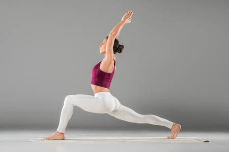 young woman practicing yoga, standing in Warrior one exercise, Virabhadrasana I pose
