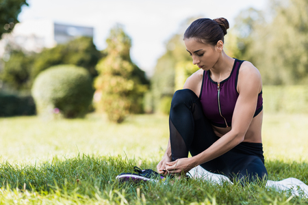 young athletic woman lacing shoes while sitting on grass Stockfoto