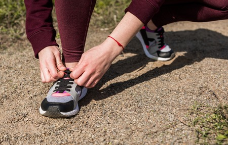 cropped shot of young woman lacing shoe before jogging Stockfoto