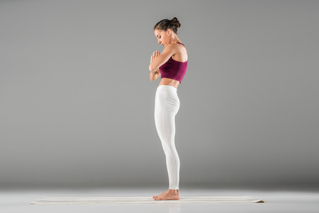 woman practicing yoga, standing in mountain exercise, Tadasana pose