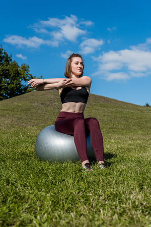 young athletic woman working out with fitball outdoors