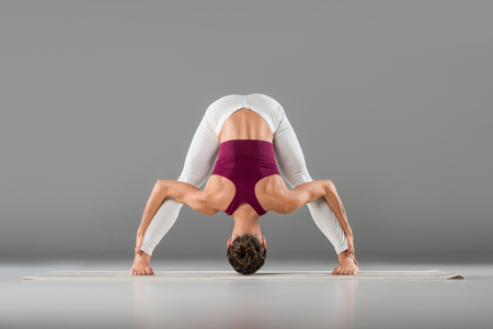 woman practicing yoga doing standing straddle forward bend pose, Prasarita Padottanasana