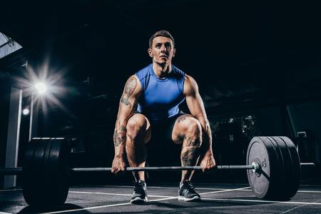 Joven deportista atlético en ropa deportiva en cuclillas mientras levanta una barra con pesas