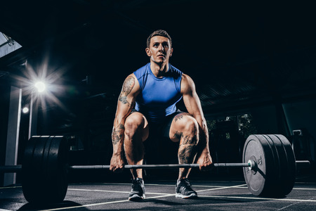 Young athletic sportsman in sportswear squatting while lifting up a barbell with weights