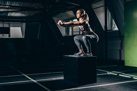 Fit sportswoman exercising in gym, doing squats on a cube