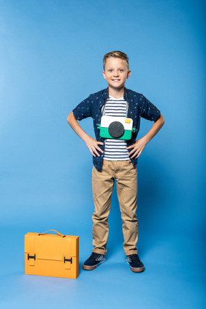 adorable little boy with paper camera standing with briefcase and smiling isolated on blue