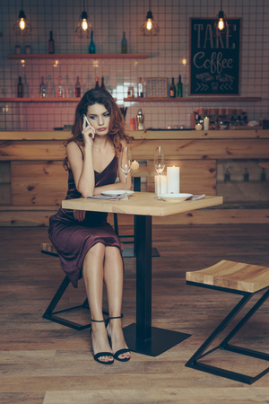 upset woman in stylish dress talking on smartphone while waiting boyfriend in restaurant
