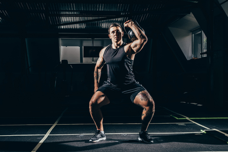 Athletic sportsman exercising in gym, lifting up kettlebell Stock Photo