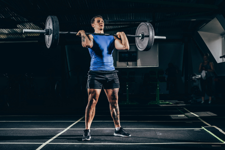 Young athletic sportsman with embossed muscles lifting up a barbell with weights at gym