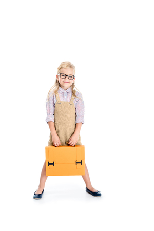 beautiful little girl in spectacles holding briefcase and smiling at camera isolated on white 版權商用圖片