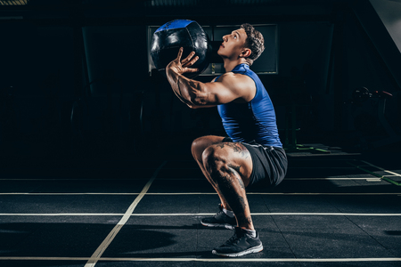 Young athletic sportsman squatting while exercising at gym with a weighted ball Stock Photo