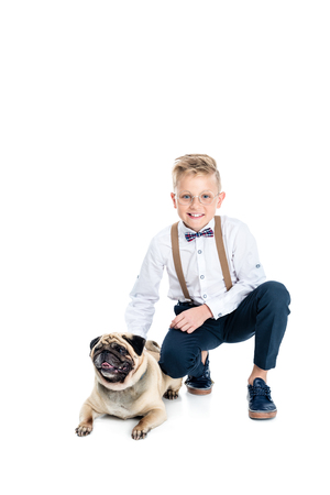 happy little boy in eyeglasses stroking dog and smiling at camera isolated on white