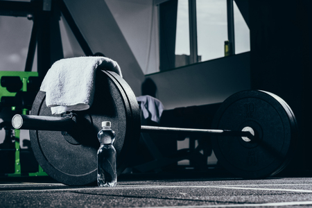 Barbell, towel and bottle of water on floor in gym