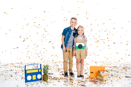 happy little kids smiling at camera while standing with various objects under falling confetti