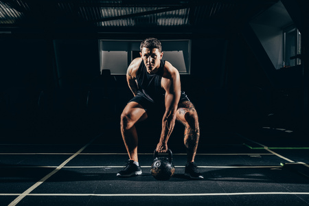 Athletic sportsman exercising in gym, squatting before lifting up kettlebell and looking at camera