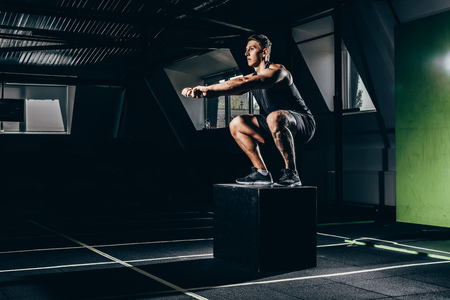 Fit sportsman exercising in gym, doing squats on a cube 스톡 콘텐츠