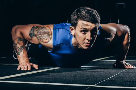 Young athletic sportsman with tattoos and embossed muscles doing push ups
