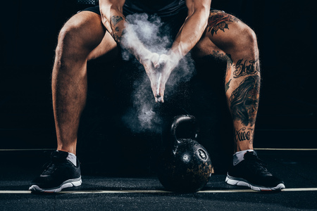 Cropped shot of young athletic sportsman applying talcum powder to his hands before exercising with kettlebell