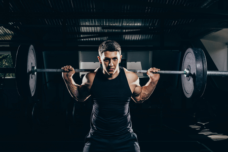 Athletic sportsman lifting a barbell with weights at gym and looking at camera