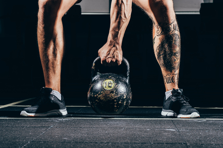 Cropped shot of athletic sportsman with  exercising in gym, lifting up kettlebell