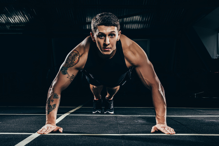 Athletic sportsman in sportswear doing push ups and looking at camera