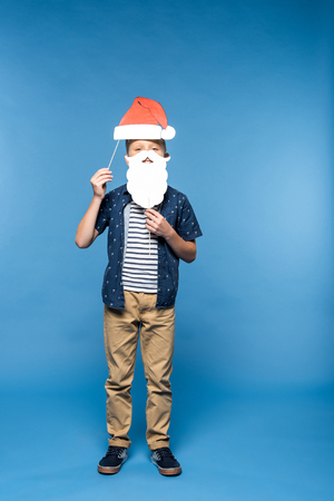 cute little boy holding paper santa hat and fake beard isolated on blue