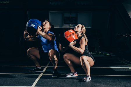 Young athletic man and woman squatting with weighted balls at gym Foto de archivo - 102341528