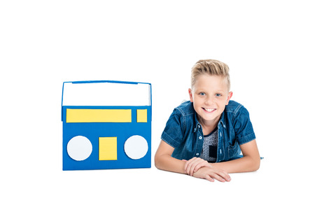 happy little boy lying with papercraft tape recorder and smiling at camera isolated on white