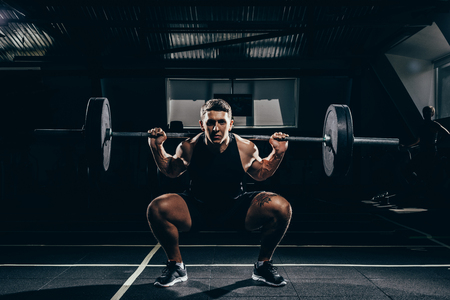 Athletic sportsman squatting while lifting a barbell with weights at gym and looking at camera