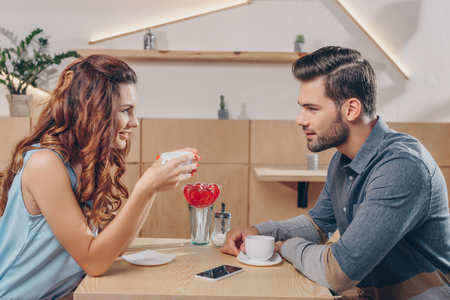 side view of couple drinking coffee while spending time together in cafe Stok Fotoğraf