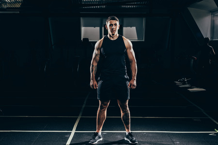 Fit sportsman with embossed muscles standing in gym and looking at camera