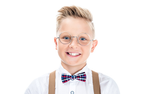portrait of beautiful little boy in eyeglasses smiling at camera isolated on white