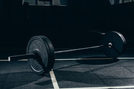 Closeup shot of barbell with weights on floor in gym