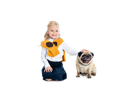 adorable little girl stroking dog and smiling at camera isolated on white