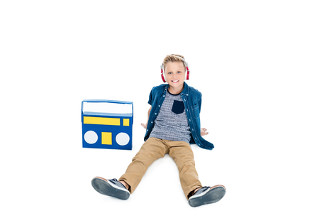 happy little boy in headphones listening music with tape recorder isolated on white