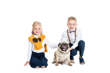 adorable little children stroking dog and smiling at camera isolated on white