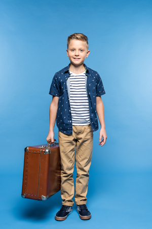 cute little boy holding suitcase and smiling at camera isolated on blue 免版税图像