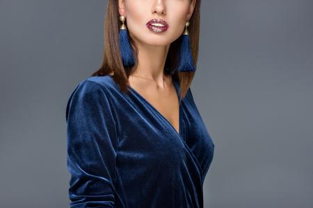 ritagliata colpo di splendida donna in abito da sera e orecchini in posa isolato su grigio