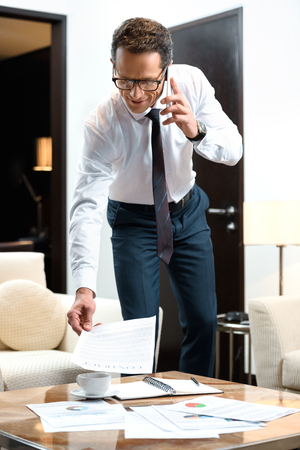 Businessman in formal wear and glasses standing over a coffee table with some paperwork on it and talking on smartphone Stock Photo