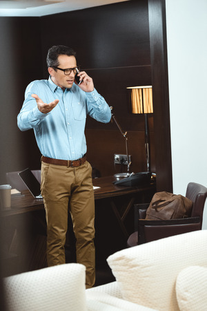 Upset businessman in business casual clothes talking on phone Stockfoto