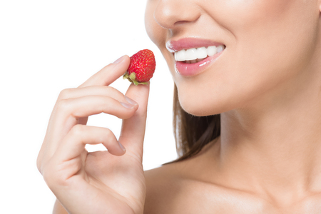 cropped shot of smiling young woman holding fresh strawberry isolated on white Stock Photo