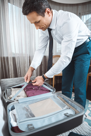 Businessman in formal wear unpacking his suitcase in hotel room