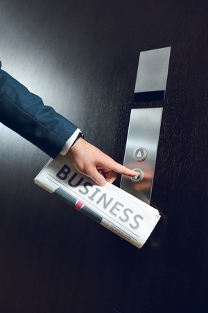 Cropped shot of businessman in hotel corridor with a newspaper in his hand, pushing elevator button