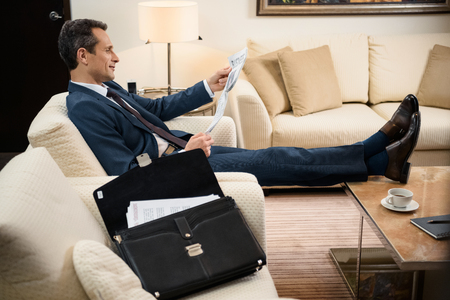 Businessman in formal suit sitting in armchair and reading a newspaper 写真素材
