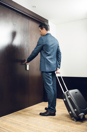 Businessman in formal suit holding a suitcase and opening hotel room door