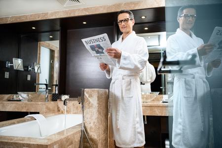Businessman wearing a bathrobe in hotel bathroom, reading newspaper while standing over bathtub