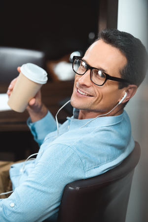 businessman in business casual clothing drinking cup of coffee and listening to music in headphones