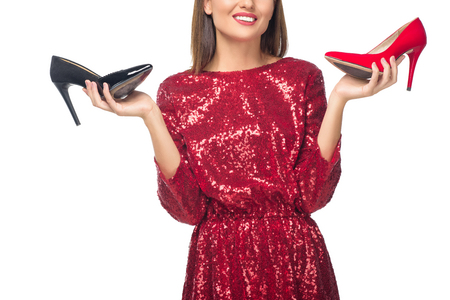 cropped shot of smiling young woman holding high heeled shoes isolated on white