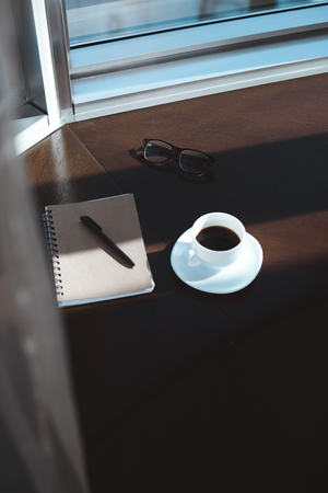 close-up view of notebook with pen, eyeglasses and cup of coffee on table
