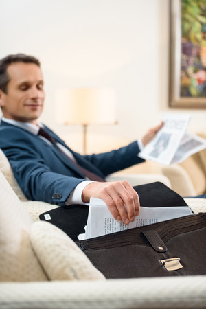 Businessman in formal suit sitting in armchair with newspaper and taking some paperwork from briefcase 版權商用圖片
